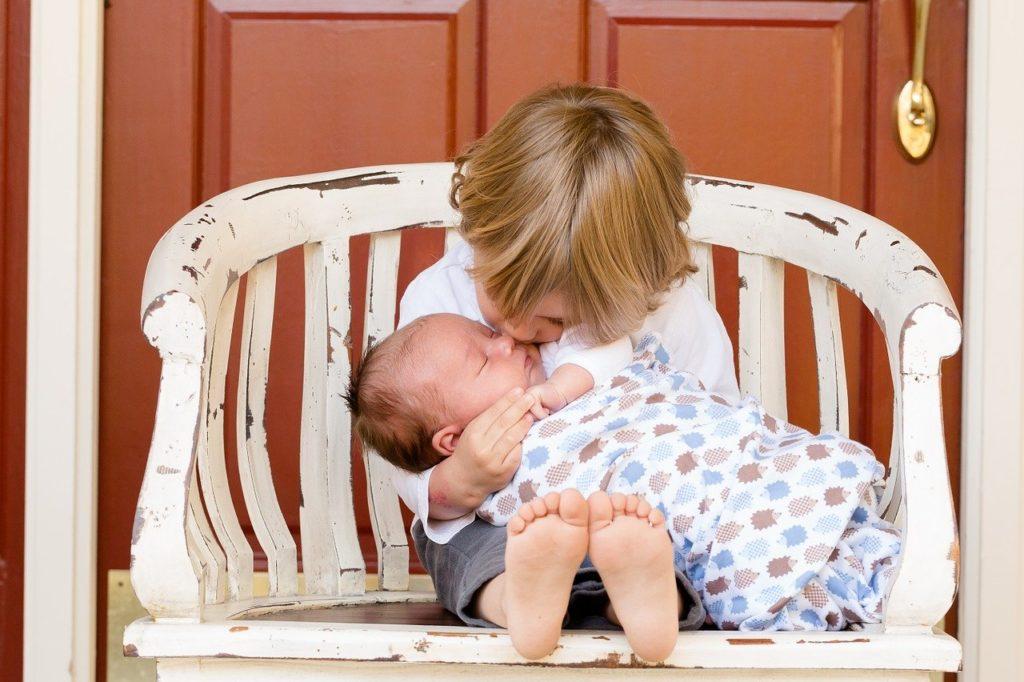 赤ちゃんを抱く子ども